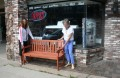Downtown Rhinelander, Inc., Executive Director Maggie Steffen, right, and volunteer Sally Latimer place one of ten new benches in front of Northland Music on Brown Street. The benches are engraved with the DRI logo.