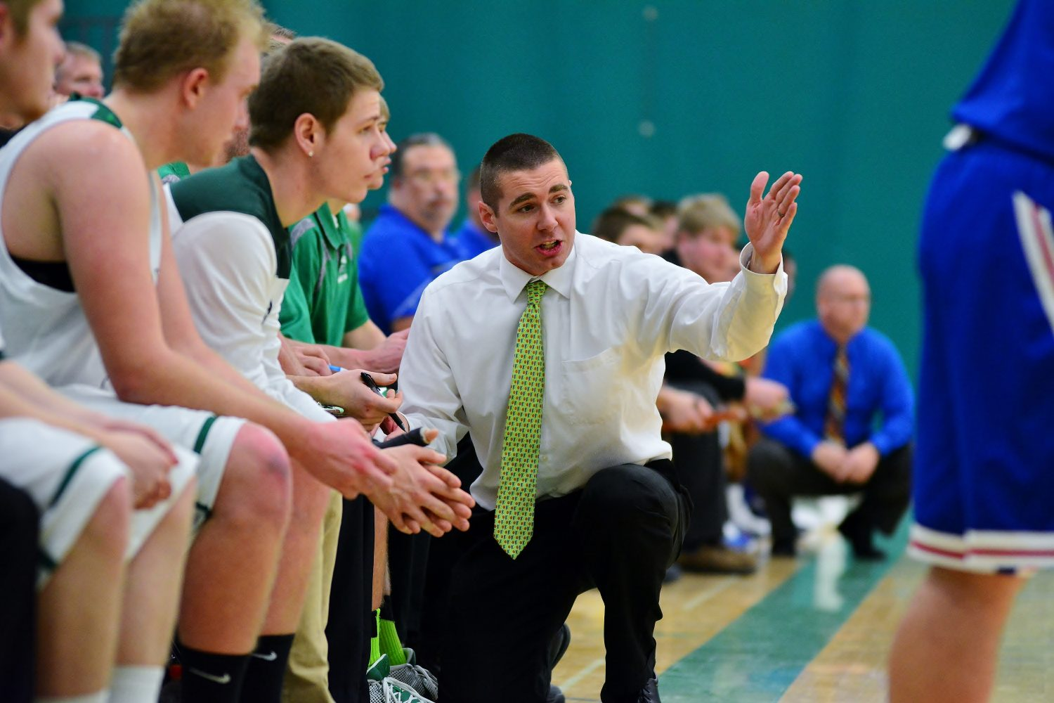 Coach Derek Lemmens gives instructions to players on the bench.