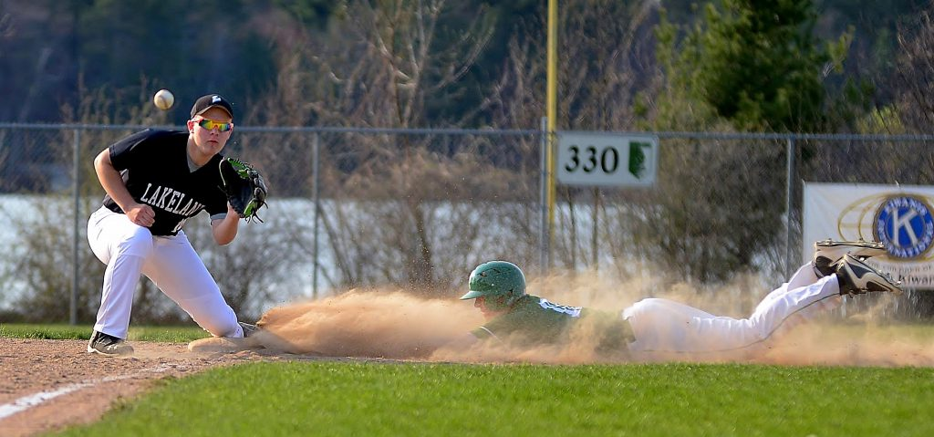 From right, the Hodags' Brandon Reinthaler dives into third base as he beats the throw to the Thunderbirds' Caleb Menzia. Photo by TMK photography