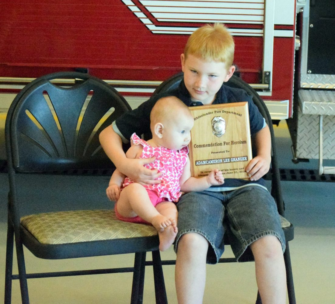 From right, Adam Cameron Lee Granger poses for pictures with his six-month-old sister, Kierra, whom he carried to safety during a house fire Tuesday in Rhinelander. The boy was recognized Friday during a program at the fire station and presented a plaque for his heroism.