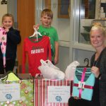 Taylor Dahlquist, left, Kadin Rodziczak and teacher Megan Biscobing show some of the pajamas donated during Pelican School's Pajama Drive. Donations of new pajamas in all sizes can be brought to the school through Dec. 15.
