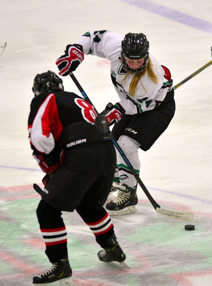 The Northern Edge's Kourtney Carrico (24) passes the puck past a Red Panther player.