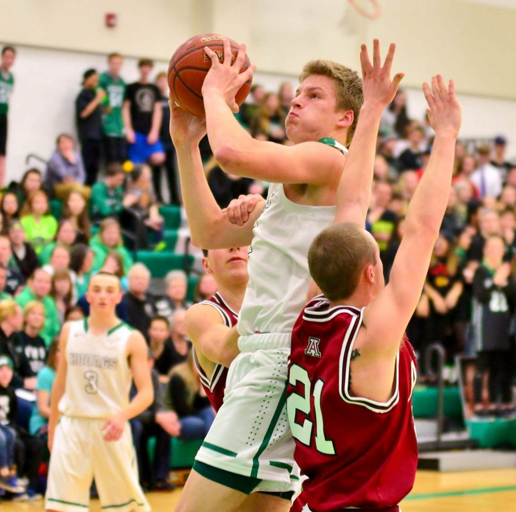 In front at left, the Hodags' Owen White drives inside for two against Antigo.