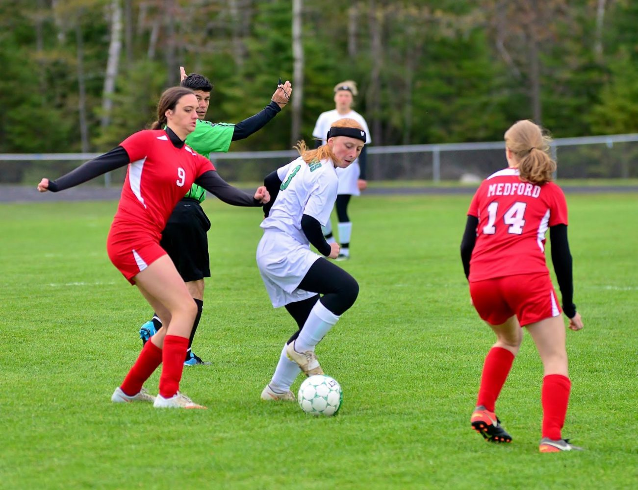 At center, the Hodags' Madeline Losch (3) advances the ball Monday between a couple of Medford players.